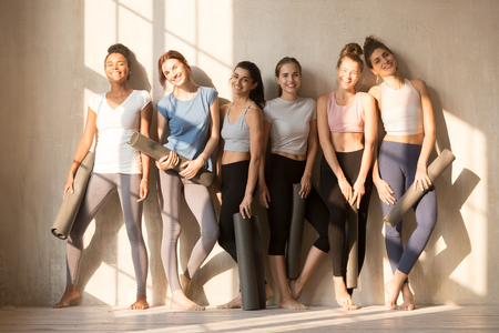 Multiracial happy sportive girls wearing sportswear stand near wall posing, hold yoga mats waiting for workout session, excited toned women laugh looking at camera, prepared for pilates class