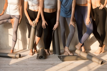 Toned female legs in sportswear stand near wall wait for yoga session together, fit girls in leggings hold mats ready for pilates training in fitness studio, athletic women in row prepared for workout