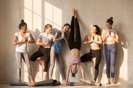 Multiracial excited girls in sportswear stand near wall wait for yoga class having fun together, happy sportive female yogi entertain play childish practicing poses, have break in training or workout 免版税图像