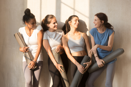 Happy diverse female yogi in sportswear hold rubber mats wait for yoga class laughing and talking, smiling multiracial toned girls chat and have fun before pilates training. Healthy hobby concept