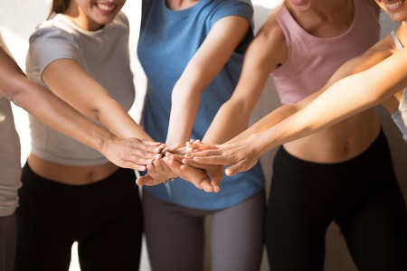 Close up of excited female yogi put hands in stack motivated for shred good sport result, smiling toned girls engaged in teambuilding activity at training, show unity and support. Teamwork concept
