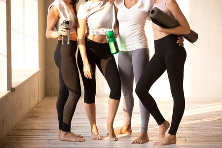 Legs of toned diverse girls standing together hugging after training in fitness studio, fit young females wearing sport leggings relax holding water bottle and yoga mat, embracing after workout Banque d'images