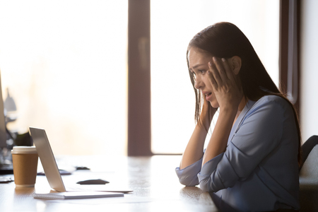 Shocked female employee sit at table, look at laptop screen frightened see mistake or error notice, frustrated woman scared experiencing system software malfunction or virus warning on computer