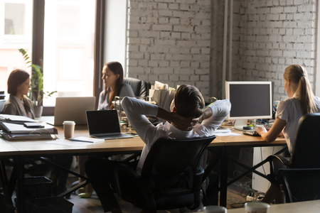 Tired male employee leaning back in chair relaxing at workplace, exhausted worker stretching hands over head sitting at coworking table with colleagues, man take break working in shared workspace