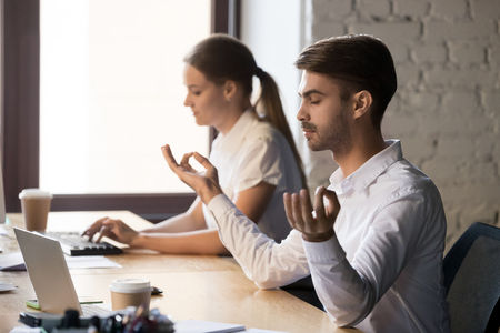 Millennial calm office worker sit with mudra hands practicing yoga at coworking workplace, peaceful male employee relaxing at shared table, meditating and controlling emotions. Stress free concept 스톡 콘텐츠 - 116391880