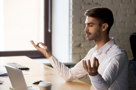 Peaceful male employee sit near laptop meditating at workplace with eyes closed, calm worker practice yoga in office, controlling emotions, businessman take break from work. Stress free concept 스톡 콘텐츠 - 116391911