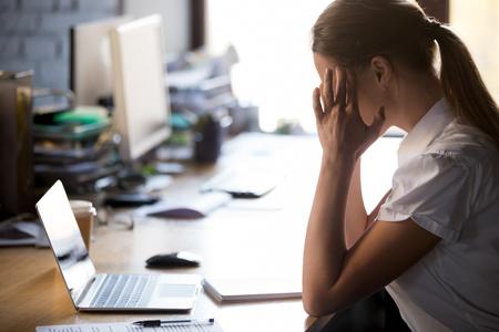 Uitgeputte vrouwelijke werknemer zit aan een bureau en masseert tempels, lijdt aan sterke hoofdpijn, vermoeide vrouwelijke werknemer voelt zich slecht met migraine of hoge bloeddruk, pauzeert van het werk ontspannen Stockfoto