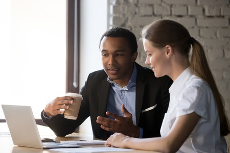 Two multiracial workers sit at office desk near laptop discussing business issues together, man and woman employee negotiate at workplace, look at computer, cooperating speak or explain ideas Stock fotó