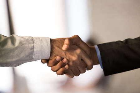 Close up of male colleagues or partners shake hands closing deal or making agreement, employees or workers handshake congratulating or greeting with success. Cooperation, partnership concept