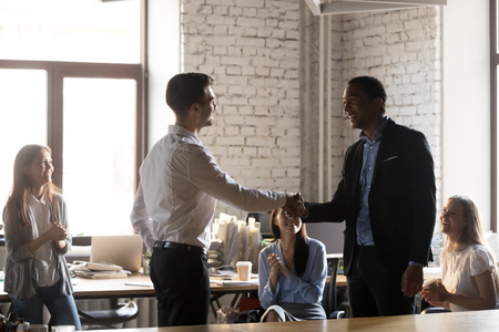 Smiling millennial businessman shake hand of male colleague congratulating with success or personal achievement, team leader handshake happy employee greeting with job promotion or employment Stock Photo