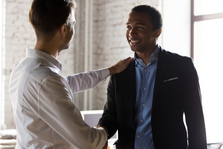 Millennial Caucasian boss handshake tap shoulder of African American employee greeting with work success, businessman shake hand of black colleague or worker congratulate with employment