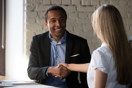 Excited multiracial business partners shake hand congratulate after successful negotiations, happy African American businessman handshake female job applicant greeting at interview. Employment concept
