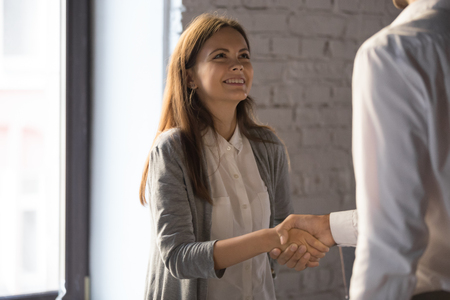 Businessman shake hand of excited female employee greeting with job promotion or employment, male boss handshake happy young woman worker congratulating with success or achievement in office