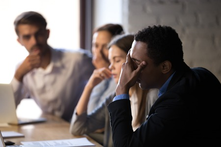 Disappointed diverse workers sit at office table, feel down reading bad company news online, depressed employees witness market bankruptcy or lose deal with customer, stressed colleagues have problem