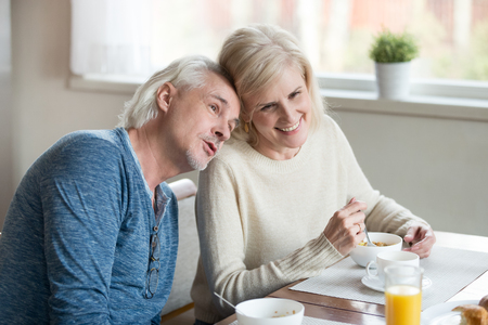 Old married couple sitting at dining room eating healthy breakfast spending time, senior husband put his head on wife shoulder telling about wishes dreaming together planning future with beloved woman
