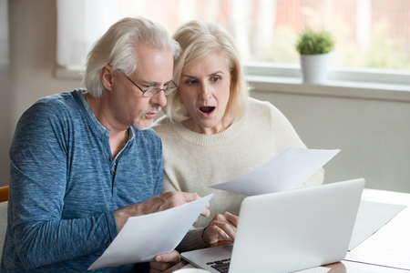 Stressed mature couple wife and husband sitting at table check unpaid bills and taxes, received bank account balance. Bankruptcy, debt and lack of money, financial problems in retirees family concept