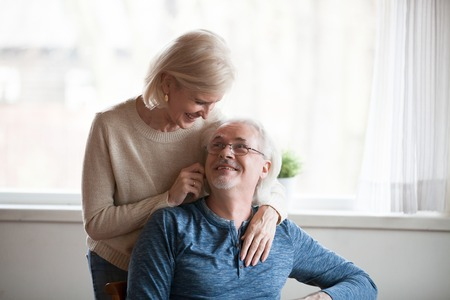 Middle aged attractive grey haired spouses loving couple wearing casual wear spending time together at home. Mature male sitting on chair his wife leaned over to her husband hugging him from behind