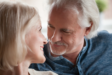 Close up faces senior woman man happy spouses portrait. Grey haired mature husband with moustache and small beard looking at beloved middle aged blonde wife. Retired people true love and care concept Stok Fotoğraf