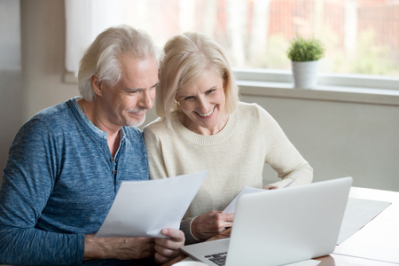 Happy mature couple retiree family reading good news received letter from bank. Satisfied senior wife and husband feels happy checking financial statement use pc, having enough money for paying bills