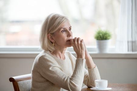 Vrouw brengt tijd alleen thuis door, zittend aan tafel met een kopje thee, vouwt de handen op de kin, verloren in gedachten. Oude eenzame vrouw heeft gezondheidsproblemen of denkt aan het leven, haalt herinneringen op aan het verleden en herbeleeft herinneringen
