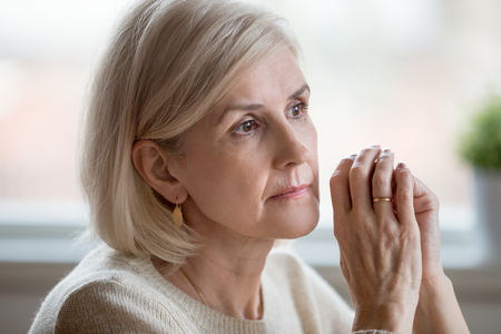 Close up portrait of beautiful sad woman folding hands together near her face, thinking about life. Aging is period of physical decline and senile dementia, mental disorders emotional problems concept