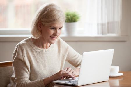 Mooie oude vrouw in vrijetijdskleding die vrije tijd thuis doorbrengt, aan tafel thee drinkt, uitrust met pc, een bericht typt aan een vriend of op internet surft, recepten zoekt, nieuws online leest