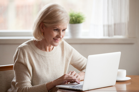 Pretty aged woman wearing casual clothes spending free time at home sitting at table drinking tea resting using pc, typing message to friend or surfing internet searching recipes reading news online