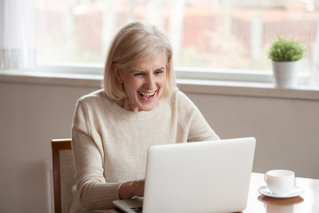 Alone middle aged mature cheerful woman in casual clothes sitting at table in the kitchen drinking tea or coffee using computer messaging with friend sharing funny videos and news communicating online.