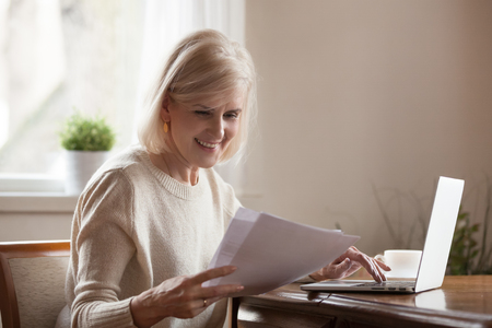 Happy blond positive aged woman sitting alone at home at desk holds received document reading good news, notification paper checking bills or bank account balance statement feeling satisfied and glad Stock Photo