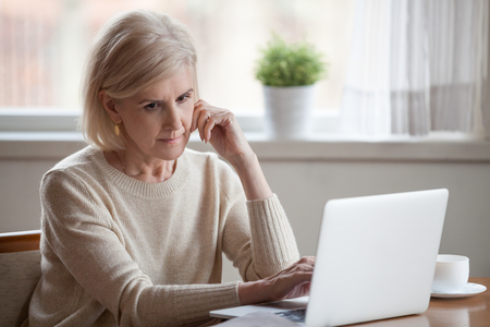 Frustrated grey hair sad middle aged woman sitting at table using computer. Distracted grandmother thinking about financial difficulties or health problems having doubts thinking feels lonely and lost