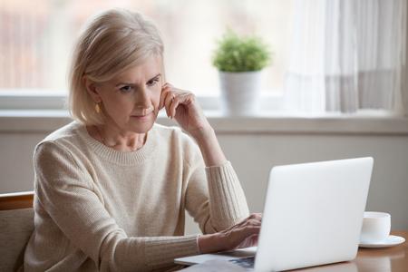Frustrato capelli grigi triste donna di mezza età seduta a tavola utilizzando il computer. Nonna distratta che pensa a difficoltà finanziarie o problemi di salute dubita pensando si sente sola e persa
