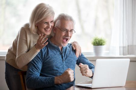 Los cónyuges de edad feliz que miran en la pantalla de la PC se sienten felices de recibir una gran noticia increíble, disfrutando de la celebración de ganar la lotería en línea. Esposa positiva senior marido descubriendo rebajas y grandes descuentos