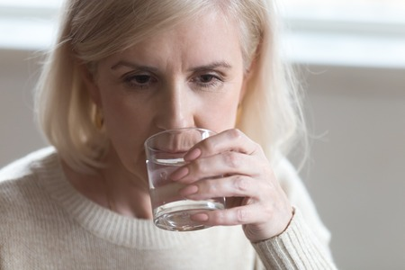 Close up portrait of blond middle aged serious woman drinking still natural water after taking a pill in the morning. Older person health care healthy lifestyle and water balance regulation concept