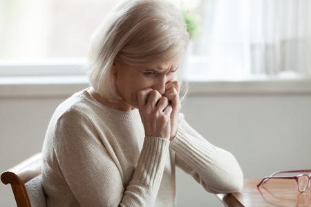 Mujer rubia de edad solitaria sentada a la mesa en casa con expresión de la cara triste cogidos de la mano cerca de la cara se siente infeliz, miserable y desesperada. Problemas de salud mental física y psicológica de los ancianos Foto de archivo