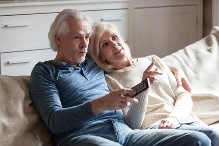 Aged surprised married couple embracing sitting on couch at country home spending weekend together, husband holding remote control from the TV and switches channels watching unexpected ending in movie