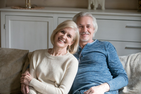 Laughing middle aged spouses in casual clothing sitting on comfy couch in living room smiling looking at camera. Head shot portrait mature grey haired happy wellbeing wife and husband shooting at home