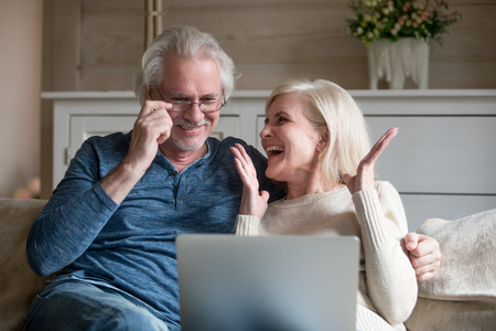Aged spouses spending time together, happy people using computer, wife clapping hands celebrating winning lottery received great news online. Mature cheerful couple watching funny video on internet