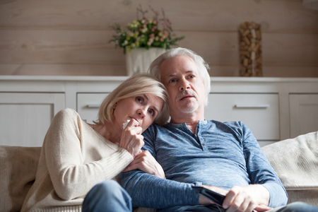 Scared confused attractive blond wife sitting on couch with grey haired husband watching thriller movie cinema. Married middle age couple spending free time looking tv show or program feels frightened
