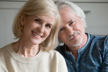 Close up portrait of mature couple loving spouses posing for camera. Blonde middle aged wife, husband with grey hair, moustache little beard shooting sitting indoors. Happy married old couple concept Stock Photo