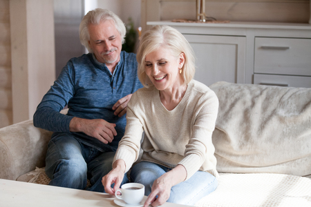 Aged friends in casual clothes woman man spending time at home housewife treats guest to tea. Blonde cheerful wife take cup with coffee while grey haired husband sitting resting on comfortable couch