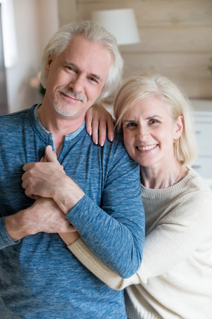 Old couple standing in living room posing for camera. Strong healthy husband hold hand of loving wife while she embracing him. Retiree people having good full life in a happy marriage, vertical image Stock Photo