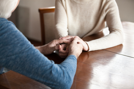 Senior middle aged spouses wife and husband couple in love sitting at table holding hands, cropped image arms close up. Body language, support of relative person, tenderness and relationship concept