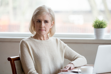 Mature grey haired depressed woman in casual cloth sitting alone at table at home opposite computer thinking about problem difficulties that has arisen, lost on thoughts feels puzzled and perplexed