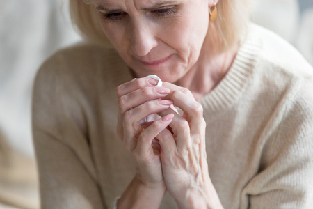 Unhappy middle aged woman folding hands together holding handkerchief crying feels bad and miserable, close up image. Sad life circumstances, death of relative person and terminal illness concept Imagens