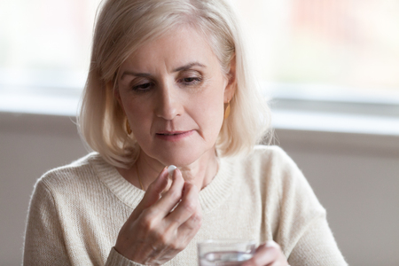 Close up of sick mature woman holding glass of still water and medical pill suffering from migraine headache feeling unhealthy and unwell. Many diseases are associated with age-related changes concept