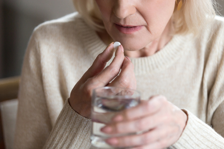Close up of unhealthy middle aged woman suffers from pain, holding pill and glass of still water feels ill taking medicine, cropped image. Disease prevention and treatment of old mature people concept 免版税图像