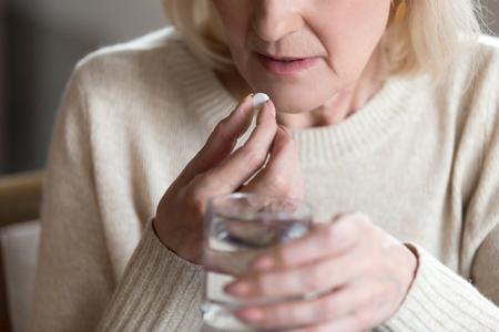 Primo piano di una donna di mezza età malsana soffre di dolore, tiene in mano una pillola e un bicchiere di acqua ferma si sente male prendendo medicine, immagine ritagliata. Prevenzione delle malattie e trattamento del concetto di persone anziane mature