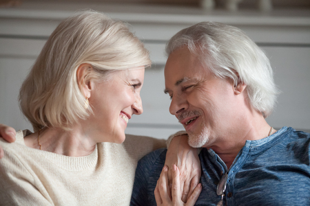 Close up portrait cheerful happy faces of aged grey haired wife and husband cuddle smiling and looking at each other with tenderness. Healthy life of old mature people or long lasting marriage concept