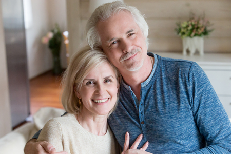 Head shot portrait happy attractive aged spouses at home posing looking at camera feeling good and healthy. Middle aged pretty husband embracing beloved wife, long lasting marriage perfect relations