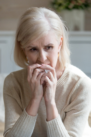 Vertical view image of blond caucasian upset middle aged sixty years woman holding handkerchief in hand sitting alone at home feels unhappy unwell miserable and anguishes mature woman mourns spouse.
